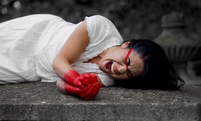 woman lies on her side, screaming in pain or grief.  Her hands are colored red, as is a strip of her face below her eye going back to her hairline.
