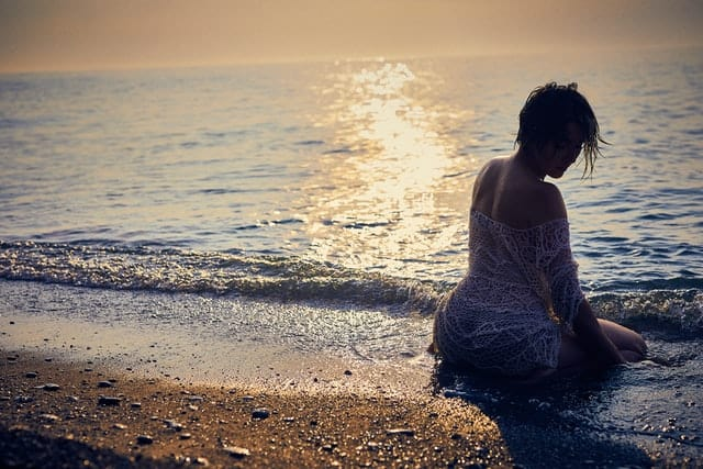 woman kneels at a beach, partway in the water.  Small waves are rolling towards her and the sound around her is drenched.