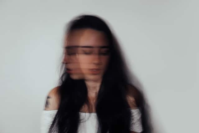 blurred image of a woman at chest-height.  While her shoulders and hair are relatively unblurred, her head appears to be in motion as if she is shaking it back and forth