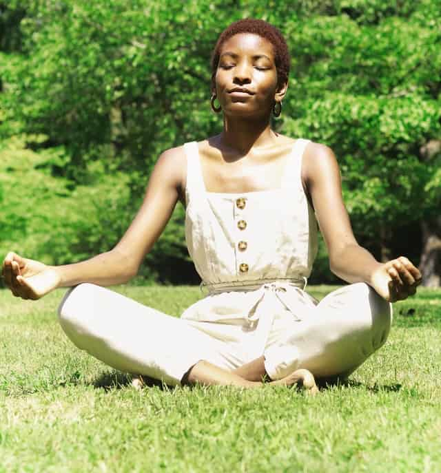 black woman sits with her legs crossed and her eyes closed.  She is outside on a grassy field with trees in the background and the sun is shining on her.