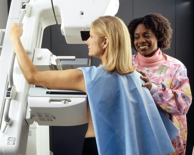 Woman gets a mamogram, with a technician helping her