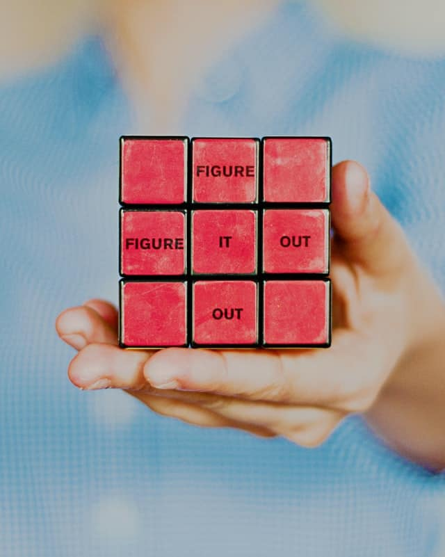 solved rubic's cube with the words 'Figure it out' typed over individual blocks, one word at a time