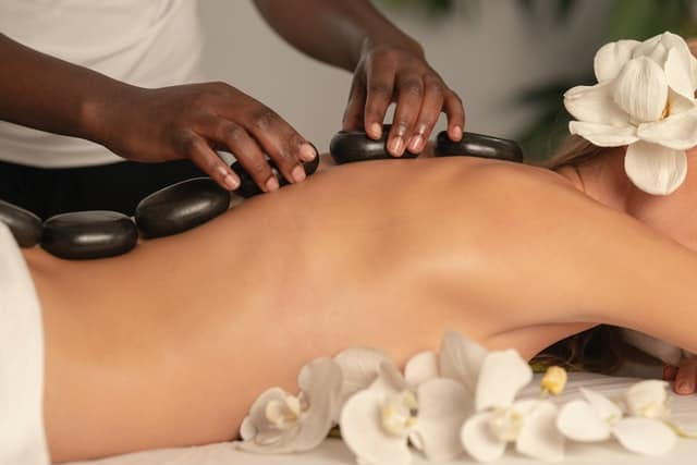 beautiful woman getting a hot stone massage.  The picture is cropped from about ear(she is wearing a white flower over her ear) to hips, with strategically placed white flowers.