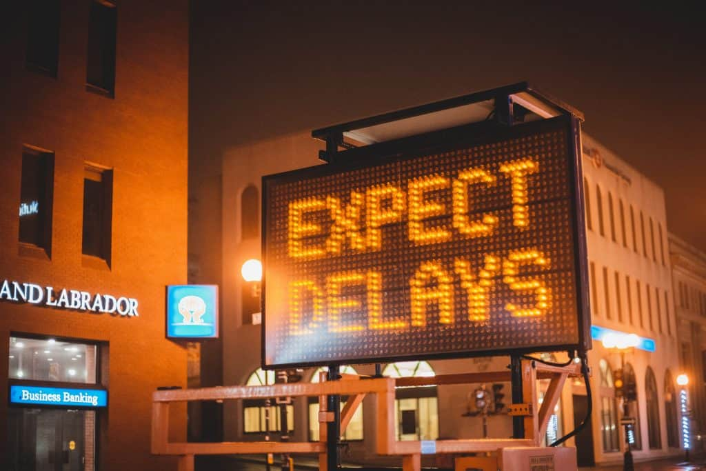A large automated sign reads 'Expect Delays'.  It appears to be on a road in a city