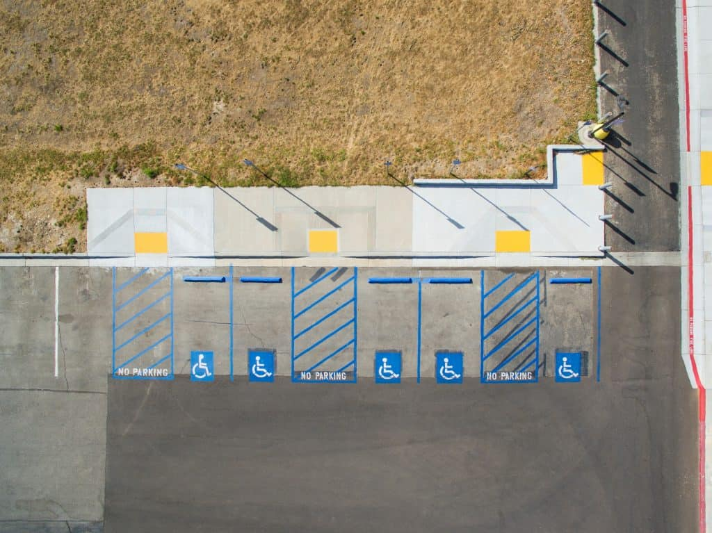 view from the air of a collection of accessible parking spaces, some with marked off spaces for wheelchair users