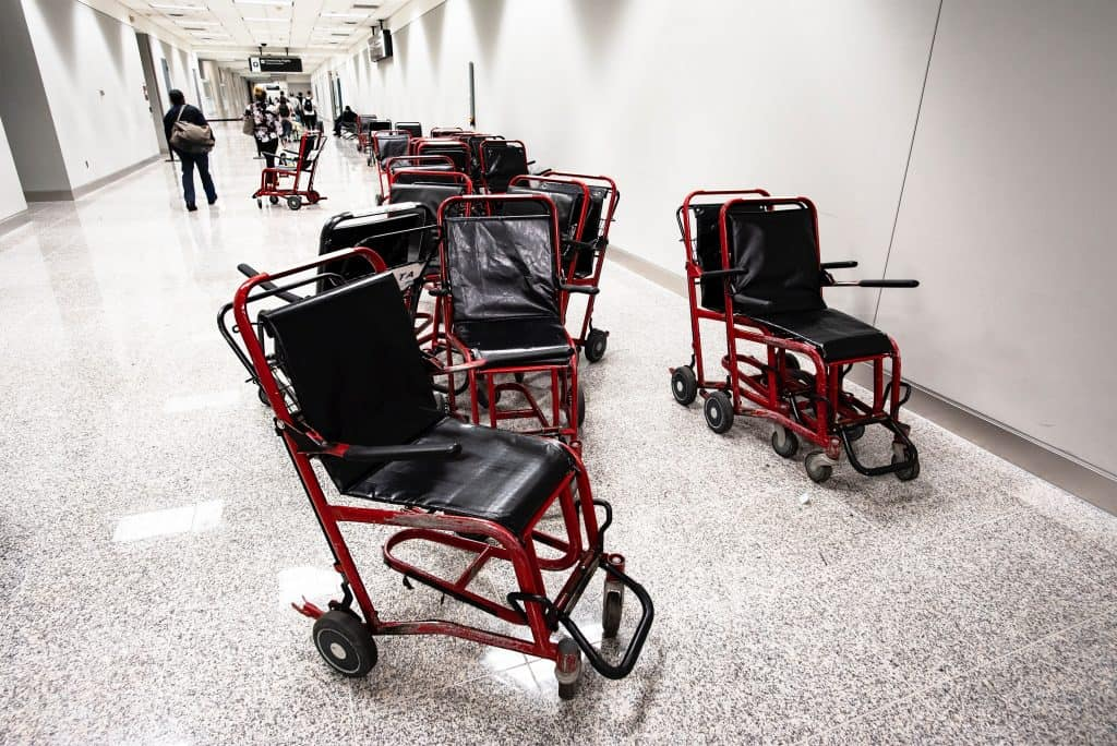 airport weelchairs lined up in a wide corridor with white walls and a white speckled tile floor