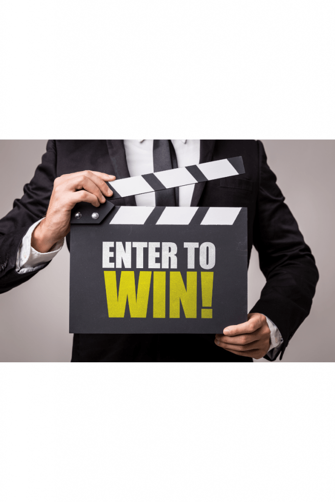 The torso of a man in a suit is visible on a gray background. He is holding a clapboard which has the words 'enter to win' on it