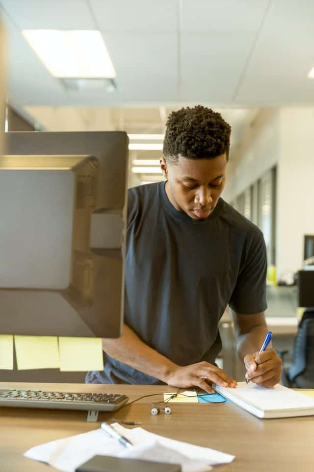 black man writes in a notebook at his work station