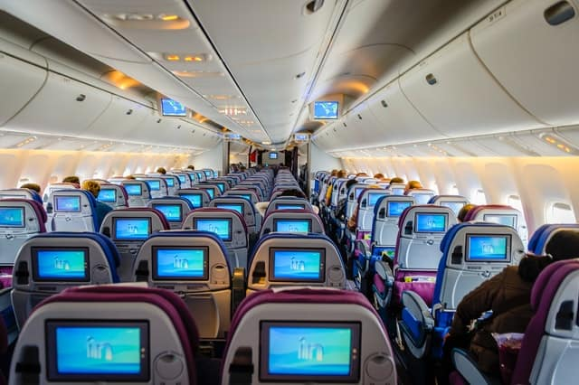 inside the plane, photo taken from near the back.  This plane has two aisles, with two seats near each window and three seats in the middle row.  Small TV moniters are on the back of each seat