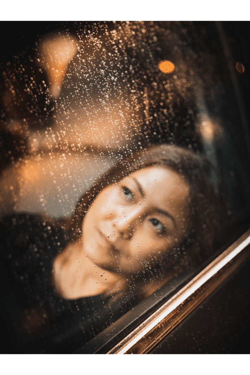 woman looks up through a car window as rain falls down. She has a thoughtful expression on her face