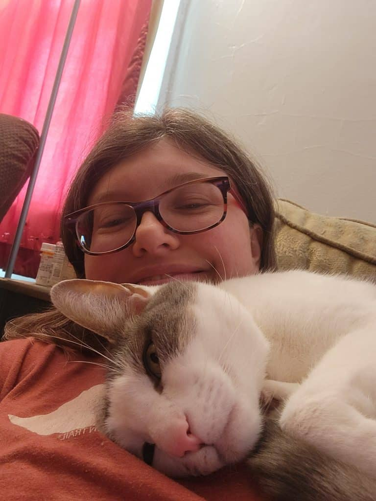 Alison smiles into the camera, half-hidden by Rorschach(gray and white cat) who is lying on her chest