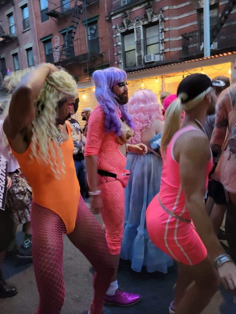 Three men in drag dancing.  All three have facial hair.  One is wearing a purple wig with pigtails and is wering a neon pink mesh outfit, the second is wearing a blonde wig with a ponytail and dressed in a neon pink tank top and shorts, and the third has a blond curly wig and is wearing a neon orange leotard and neon pink fishnet stockings.