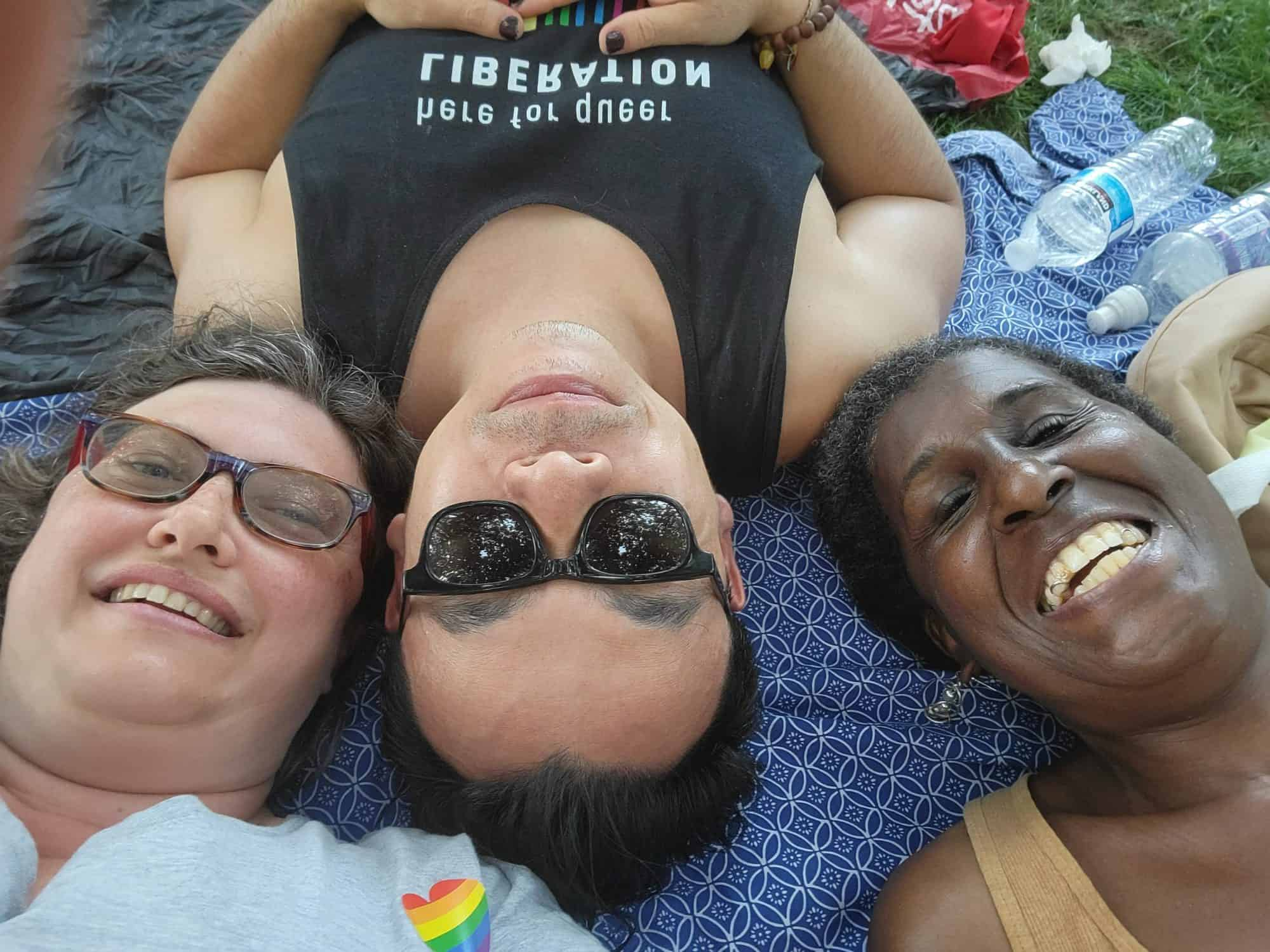 three smiling bi people. Alison is on the left(white woman with brown hair and tinted lenses), Godwin upside down in the middle(Asian man with black hair and sunglassess), and Nee on the right(Black woman with her hair natural and up). All three are smiling into the camera. They are lying on their backs, with only their faces visible.