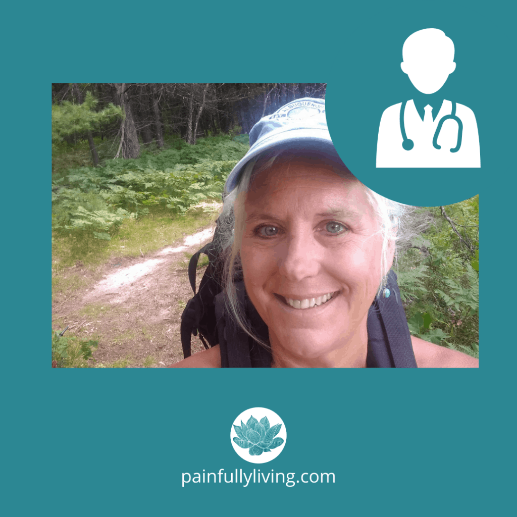 Katie Clark(white woman with white hair tucked under her hat) smiling to the camera on a nature trail with a backpack over her shoulders