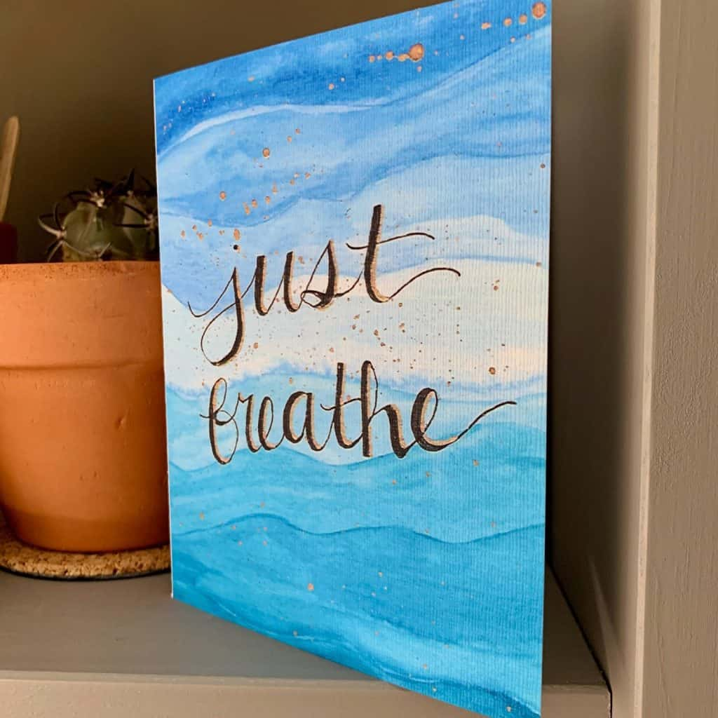 """A greeting card beside a flower pot with a succulent in it.  The card is colored in a range of blues in wave patterns.  The writing on the card is """"Just Breatheathe"""" in black cursive text"""