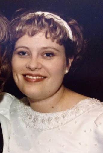 Sarah at 28, smiling while wearing a white dress with a white hairband.  The picture is cropped to be from her chest up.