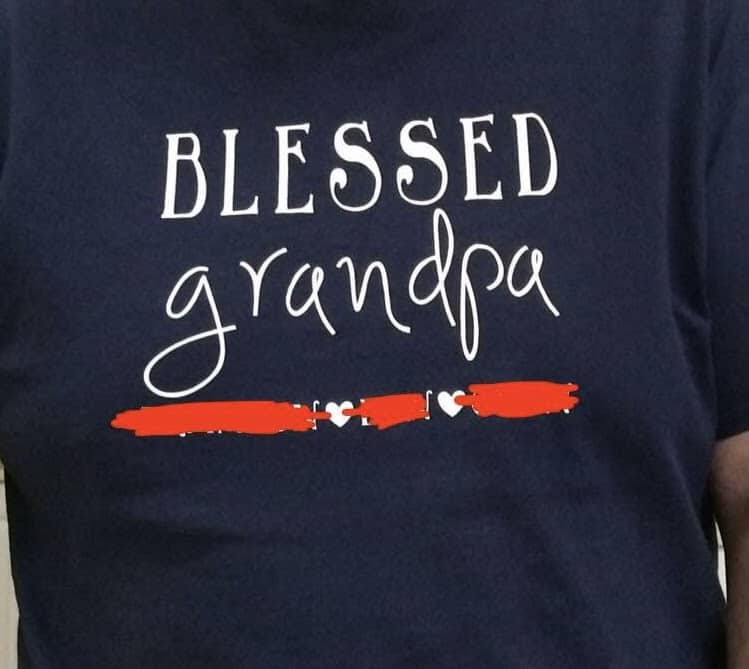 """Closeup of a dark blue shirt.  In white writing """"Blessed grandpa""""  below that, there is space for three names(covered) with hearts between them."""