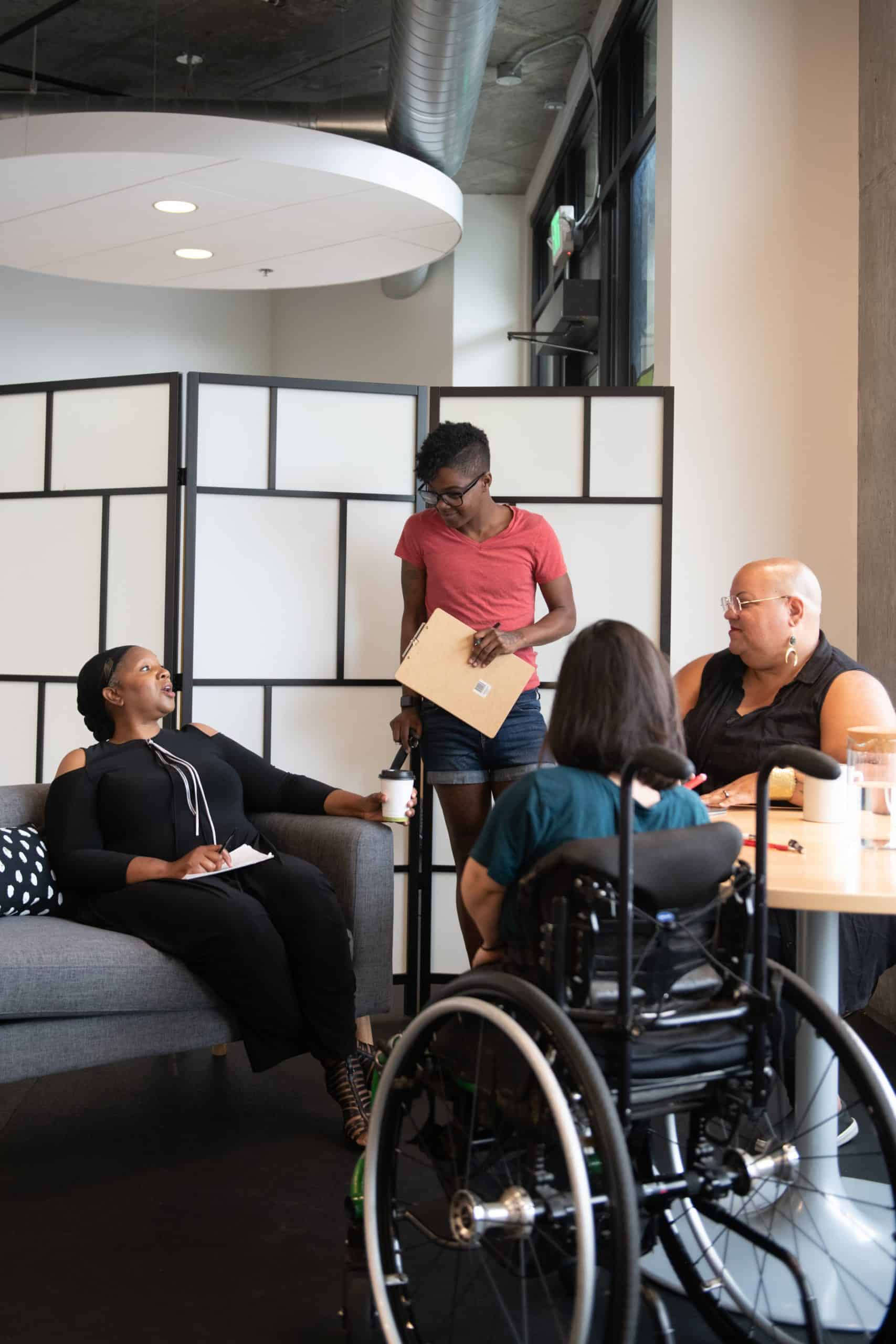 Four disabled people of color gather around a table during a meeting. A Black woman sitting on a couch gestures and speaks while the three others (a South Asian person sitting in a wheelchair, a Black non-binary person sitting in a chair, and a Black non-binary person standing with a clipboard and cane) face her and listen.