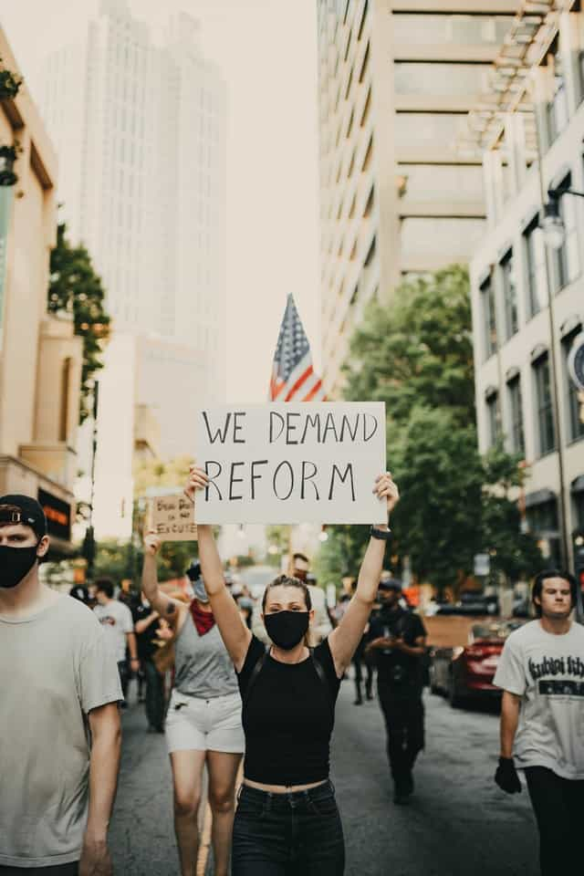 """woman dressed in black with a black face mask holds up a sign that reads """"We demand reform""""  She is part of a larger march down a city street."""