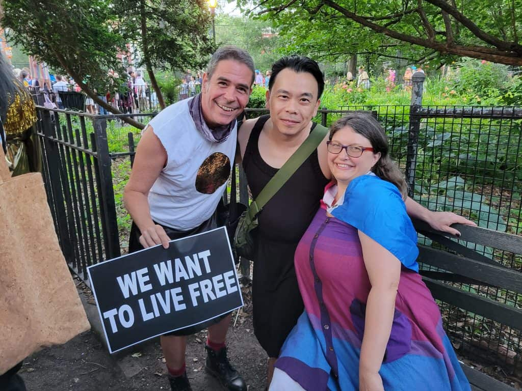 """Paul(white man wearing a white shirt and black kilt), Godwin(Asian man wearing a black knee-length dress), and Alison(white woman in a purple, pink, and blue dress) smile at the camera, with Paul holding a sign that reads """"We want to live free"""""""