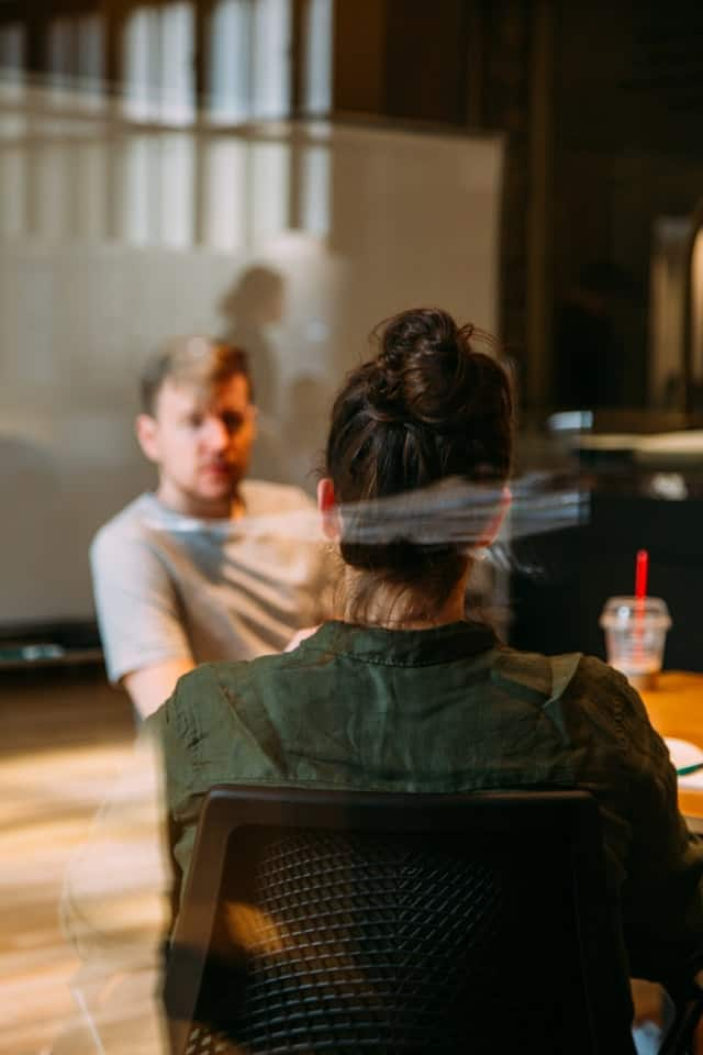 The picture is shot through a glass wall.  A woman's back is visible as she speaks with a man across the desk from her.
