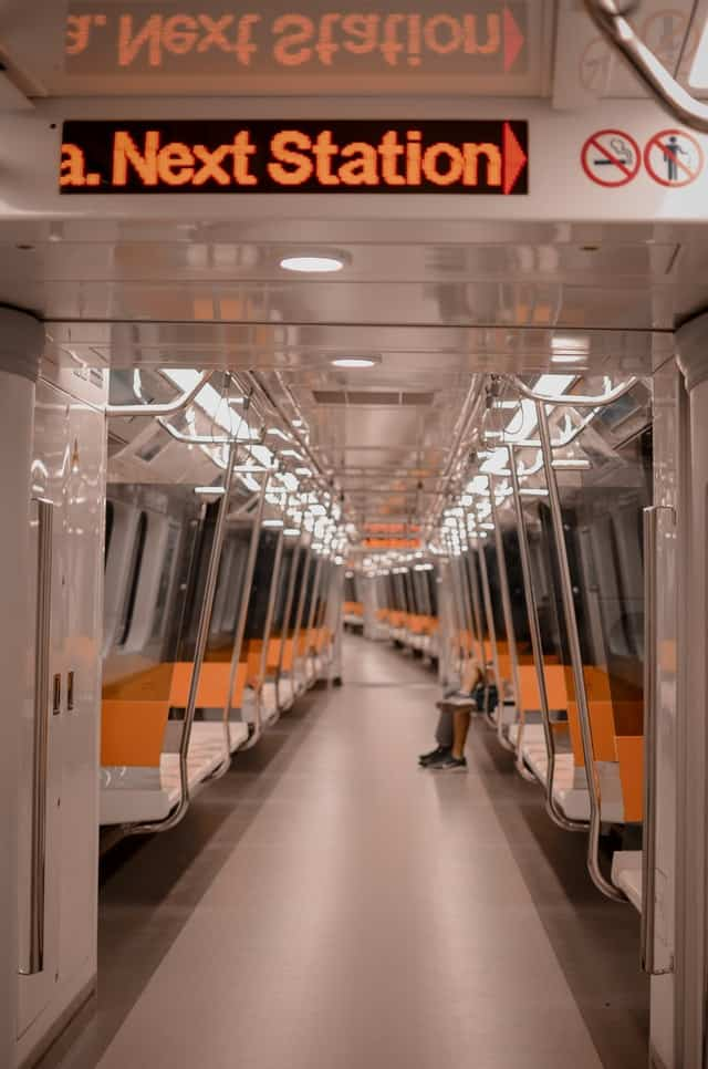 """view of a lightrail or subway car, mostly empty.  A scrolling marquee hangs from the ceiling with the words """"next station"""" visible."""""""