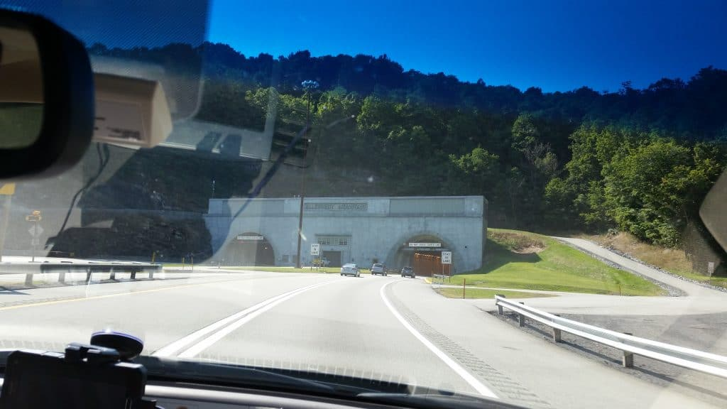 picture taken from the passenger seat of the car.  The windshield and wiper are visible in the foreground, but the focus of the picture is a multilane entrance to a car tunnel into a mountainside.