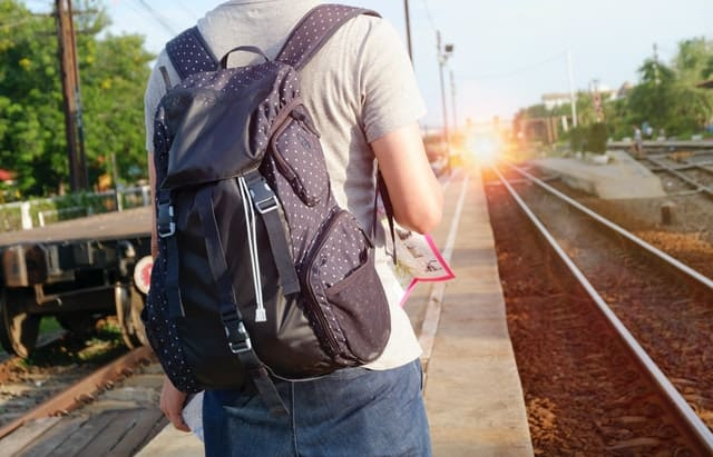 Focus on a person at a train stop.  you see their back(wearing a black backpack) and the light of an approaching train.  There are only two tracks.