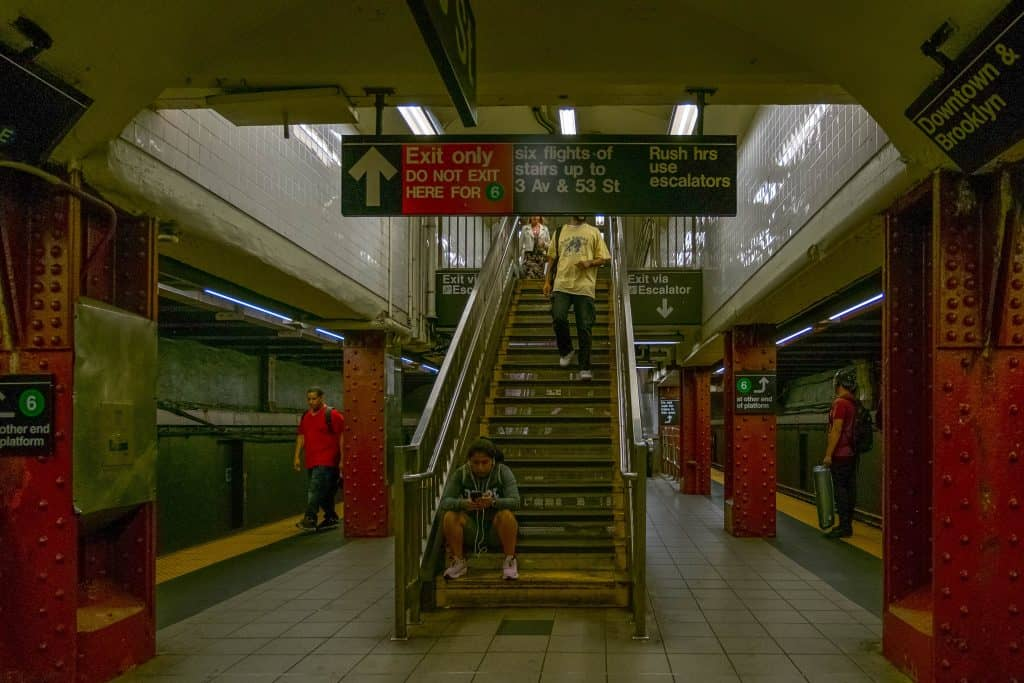 NYC subway station.  The center of the picture is a flight of steps.  The sign above it reads 'exit only' with additional information about connecting lines.