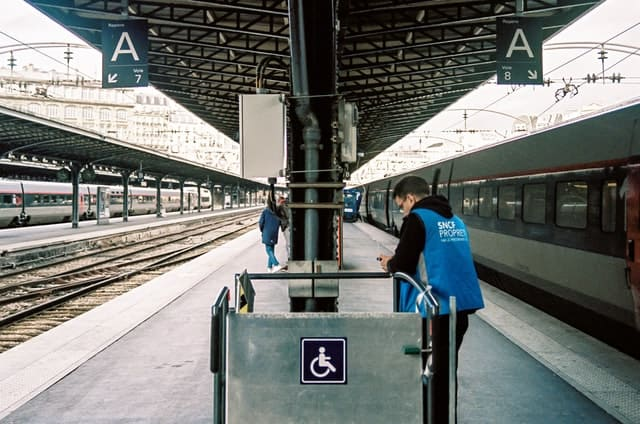 a train platform.  The focus is on a piece of equipment with an accessibility symbol