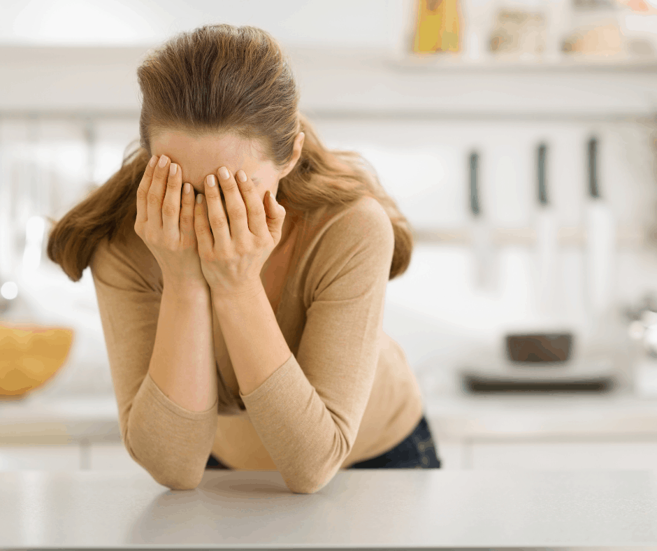 white woman holds her face in her hands.  She is in her kitchen, leaning on her counter.