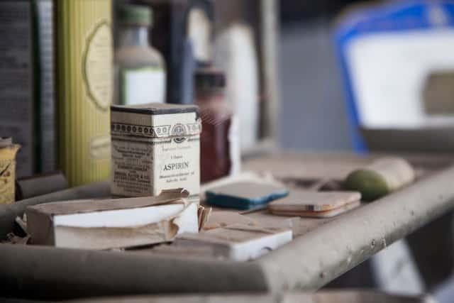 dusty shelf with old-fashioned box of aspirin on it.