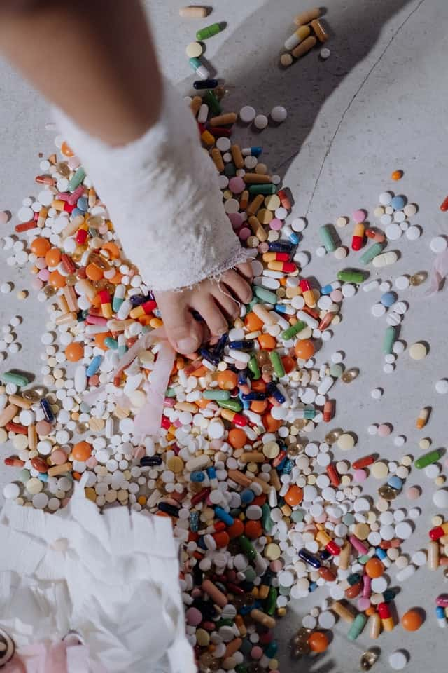 a foot in an ankle cast is visible with a variety of pills sprinkled on the floor.