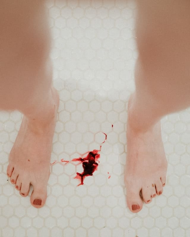 a white tiled bathroom.  A pair of legs are visible, with menstrual blood spattered between the feet.