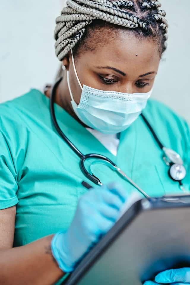 nurse writes on a clipboard