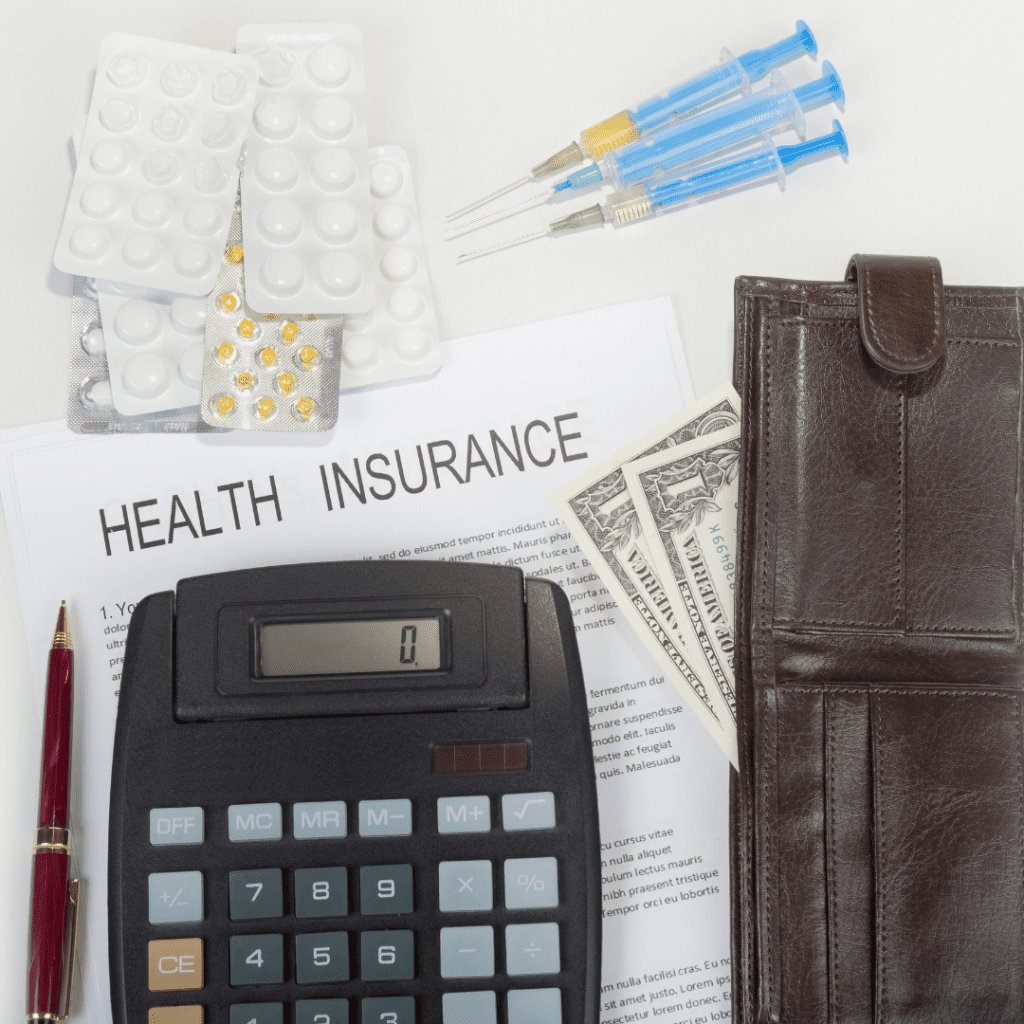 """A document titled """"Health Insurance"""" lies on a white table.  Above it is a pile of pills in blister packs.  To the left of them are a set of three syringes with liquid inside.  Down the right side of the page is a leather wallet with dollar bills peeking out.  Below the words is a calculator, with a pen to its left."""