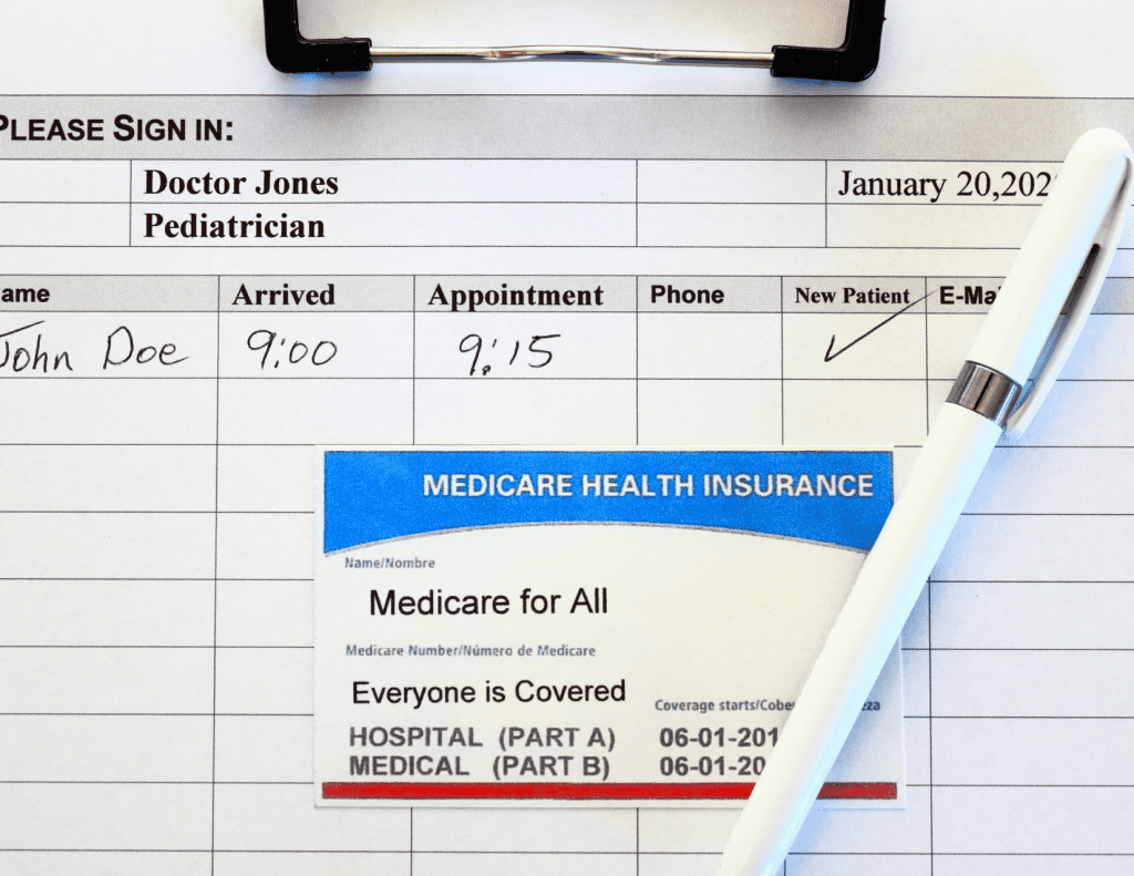 """An appointment check-in sheet is in the background, checking in  """"John Doe"""" A Medicare Card is placed on top of the check in sheet, with a white pen leaning over it.  The card  reads """"Medicare health Insurance"""" accross a blue background, then where the name should be """"Medicare for All"""", and below it where the ID number normally is it reads """"Everyone is Covered""""  The dates of coverage are partially obscured by the pen."""