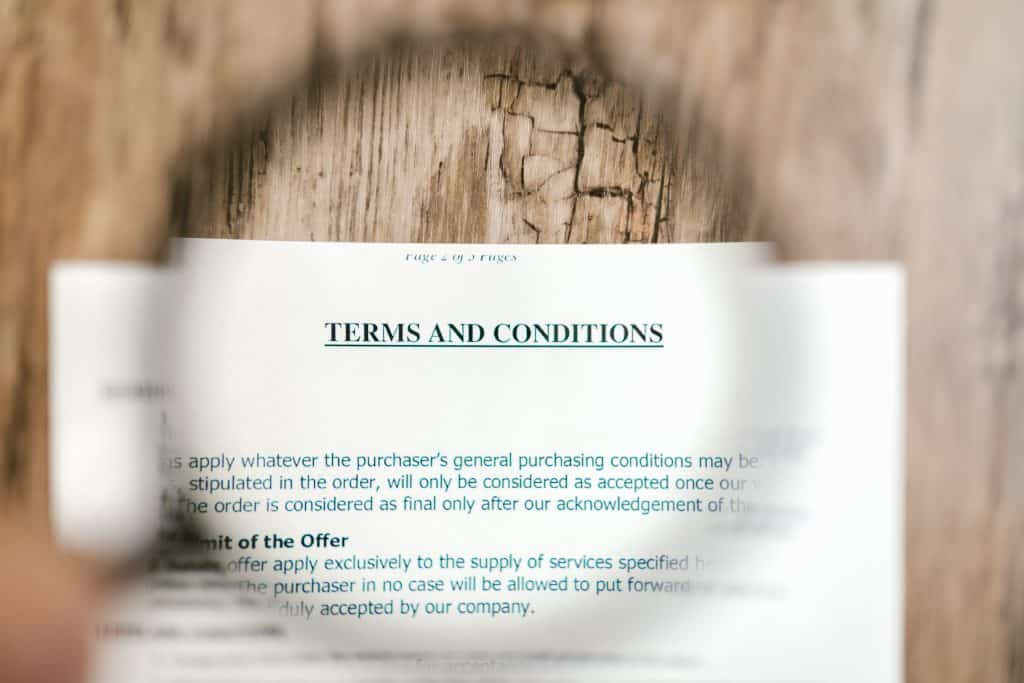 """a pile of white papers on a wooden table.  There is a circle magnifying the words that covers most of the visual area.  The top of the page reads """"TERMS AND CONDITIONS"""""""